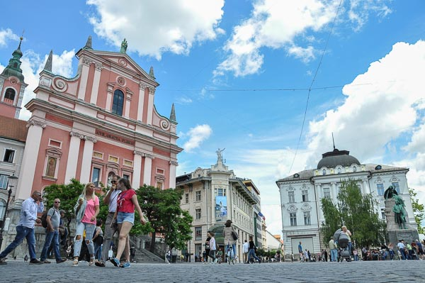 A group of people crossing Ljubljana Preseren Square with a red Church of St Francis in the back