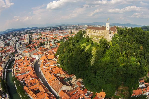 An aerial view of a green forested castle hill with medieval Ljubljana Castle anf the old town of Ljubljana